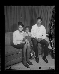 Studio Portrait of a Mother, Father and Child Sitting on a Sofa