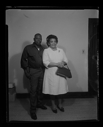 Studio Portrait of a Couple Standing, The Women is Holding her Purse