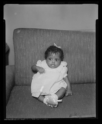 Studio Portrait of an Infant Girl Sitting on a Sofa