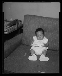 Studio Portrait of an Infant Sitting on a Sofa
