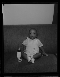Studio Portrait of a Toddler Boy Sitting on a Sofa with a Bottle
