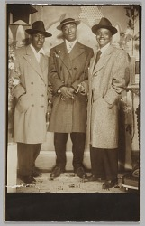 Photographic print of three unidentified men standing in hats and over coats