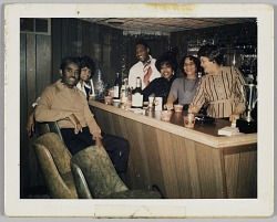 Photographic print of a group of people gathered around a bar