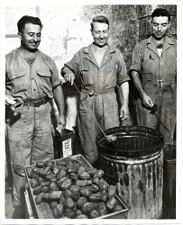 [Three men frying doughnuts in a garbage can] [black-and-white photoprint]