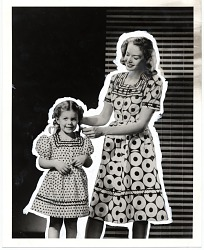 [Woman and girl dressed in similar dresses made of doughnut print fabric : black-and-white photoprint.]