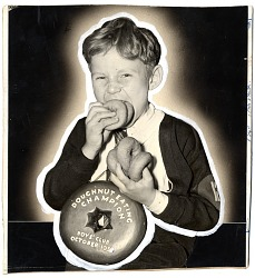 [Boy with Doughnut Eating Champion award, Boys' Club, October 1938 : black-and-white photoprint]