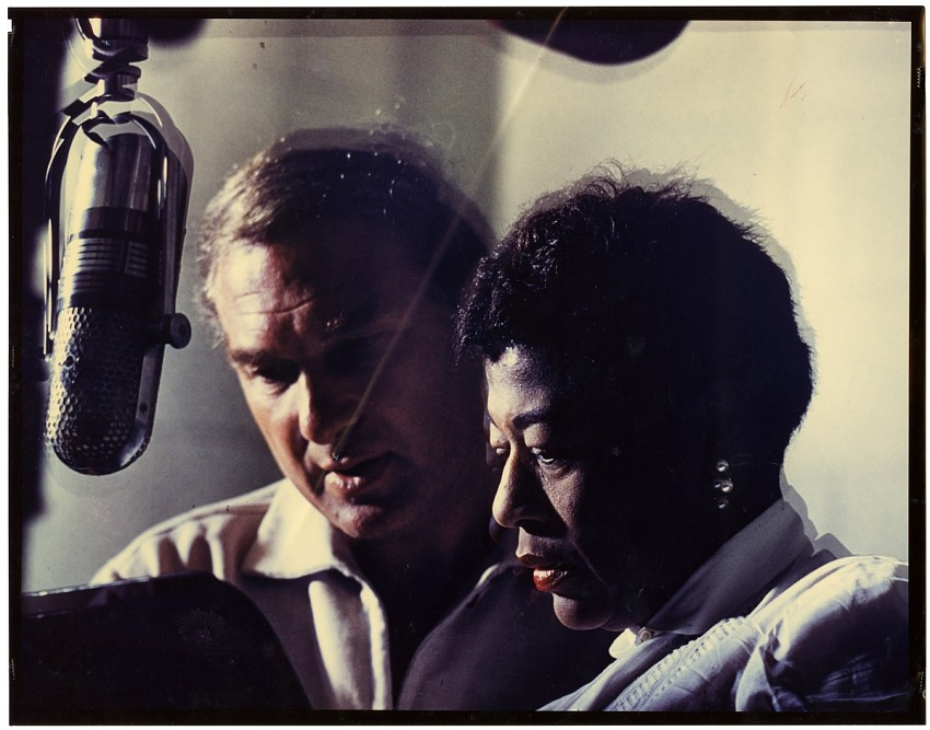 Ella Fitzgerald and Norman Granz at microphone : color photoprint.