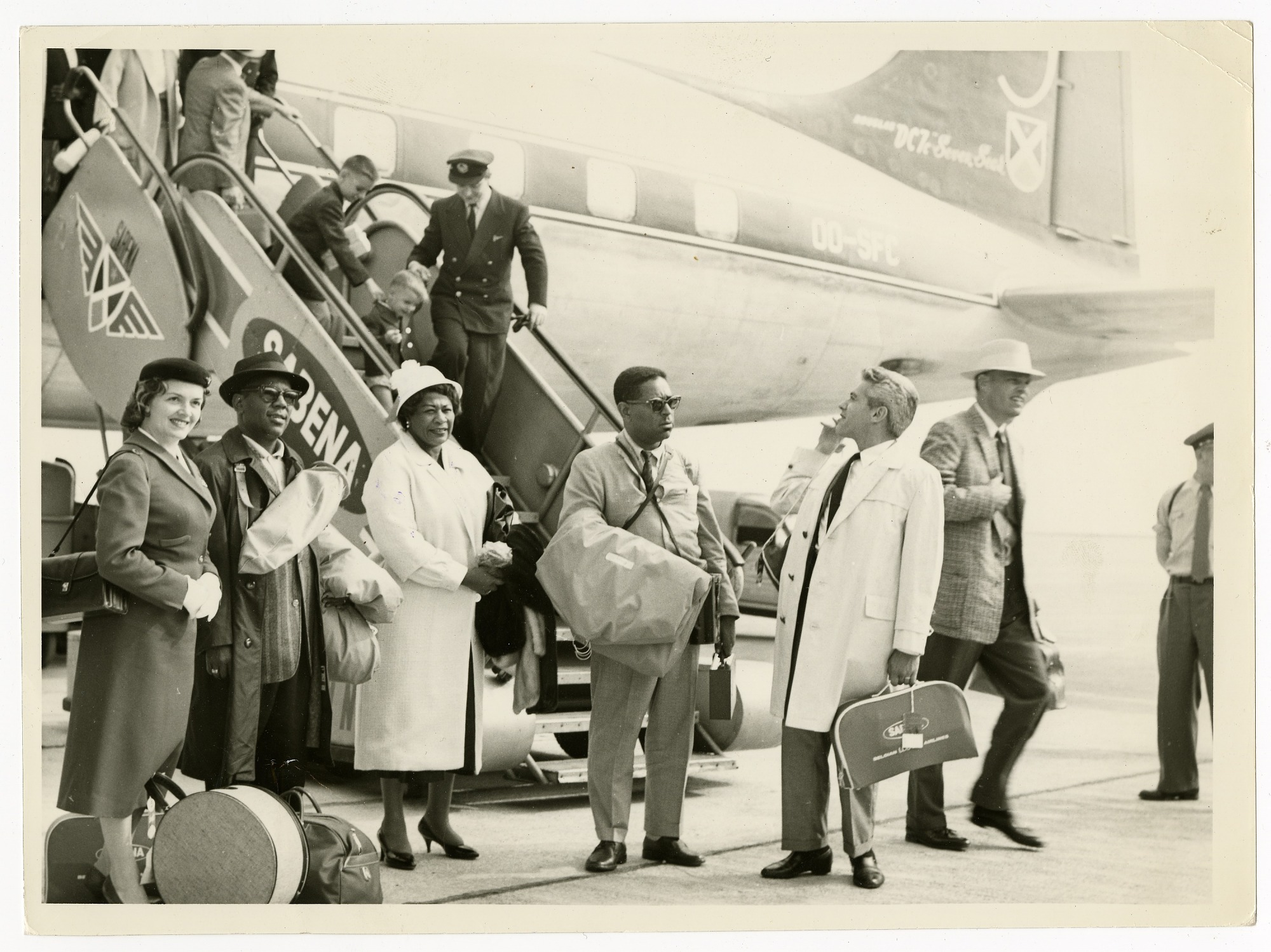 Image for Musicians and others exiting Sabena airplane. Left to right: Stewardess, Roy Eldridge, Ella Fitzgerald, Dizzy Gillespie, Lou Levy, and Paul Smith, ca. 1956. Black-and-white photoprint.