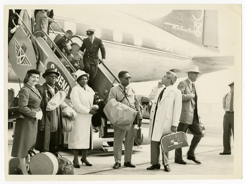 Musicians and others exiting Sabena airplane. Left to right: Stewardess, Roy Eldridge, Ella Fitzgerald, Dizzy Gillespie, Lou Levy, and Paul Smith, ca. 1956. Black-and-white photoprint.