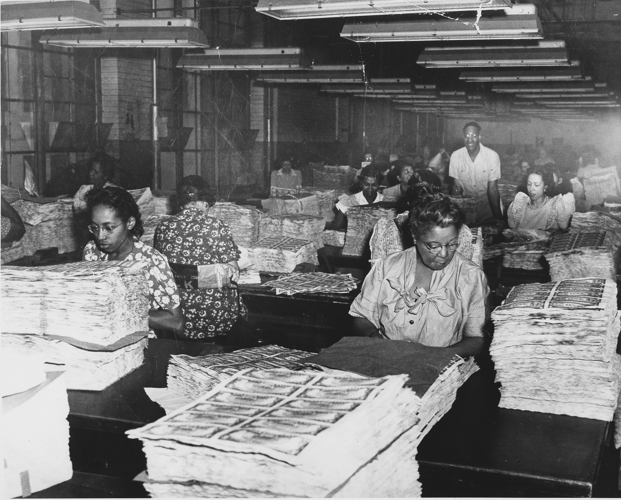 images for African American female workers at the Bureau of Engraving and Printing, with stacks of currency : paper photoprint
