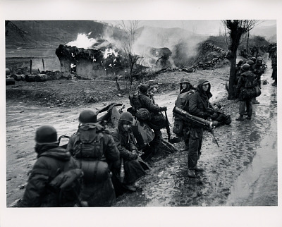 U.S. Marines pass a burning Korean village in the winter rain