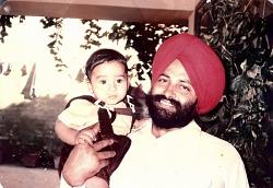 Balbir Singh Sodhi holding a male toddler.