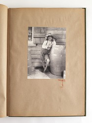 young boy leaning on a barrel