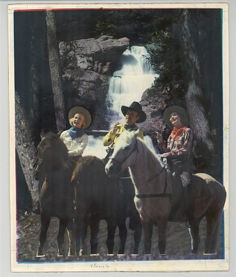 Horseback riders in front of waterfall