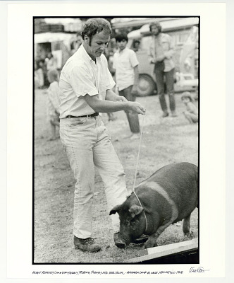 Hugh Romney (AKA Wavy Gravy) putting Pigasus into her truck. Hog Farm Camp, El Valle, NM. 1968