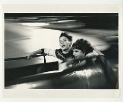 boy and a girl on a fast ride at amusement park