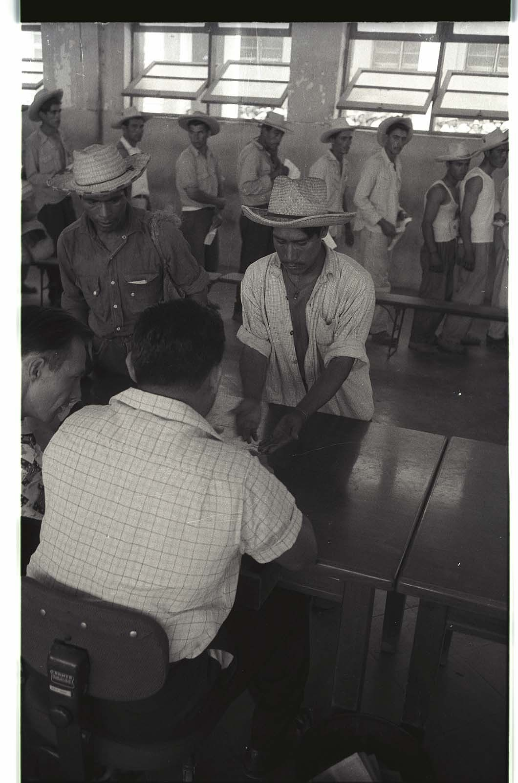 An official examines a bracero's hands for calluses during processing at the Monterrey Processing Center, Mexico.