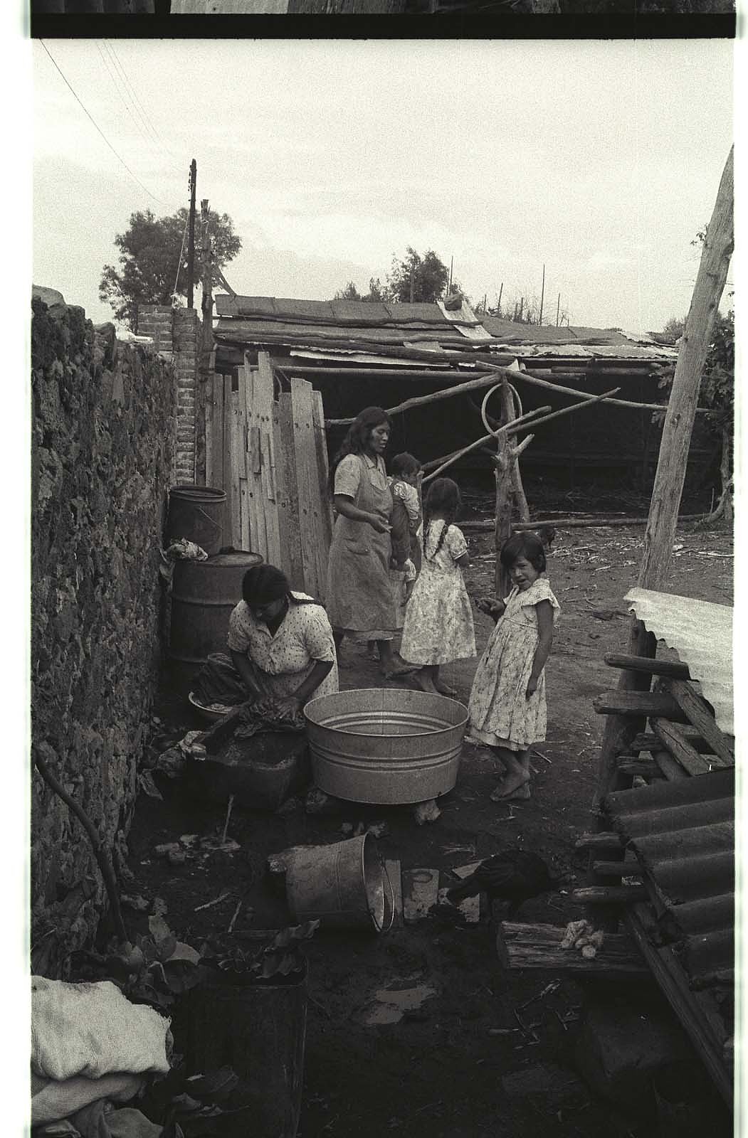 Women wash clothes and care for children in the courtyard of a bracero family home in San Mateo, Mexico