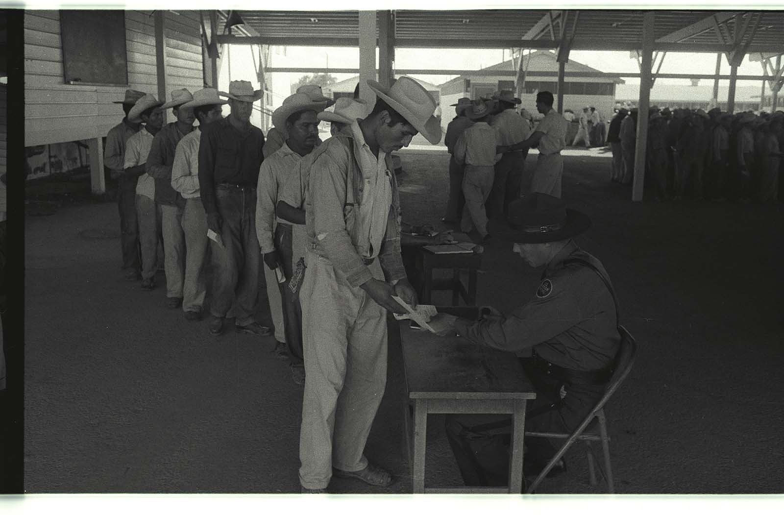 An official reviews the documents of a bracero while others wait in line to be processed at the Hidalgo Processing Center, Texas