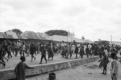 Crowd accompanying Egungun masquerader and his musicians, Ede, Nigeria, [negative]