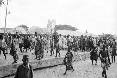 Crowd accompanying Egungun masquerader and his musicians, Ede, Nigeria, [negative]