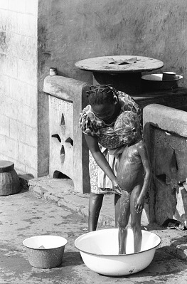 Domestic scenes in front of house of Latifu Awoyale, Ibadan, Nigeria, [negative]