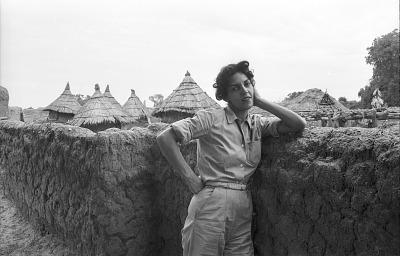 Joan Elisofon standing in front of a mud brick wall, Bin village, Mali, [negative]
