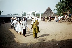 Line of players costumed as scholars, priests, or as Muslims in the njenji parade at Ezi Nwachi compound, Ndibe Village, Afikpo Village-Group, Nigeria. [slide]