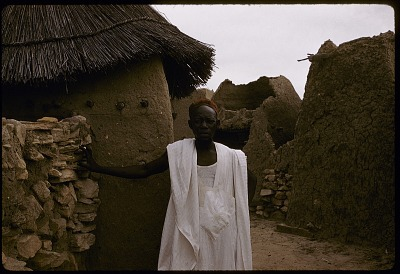 Dogon man standing by compound stone fence, Sanga, Mali, [slide]