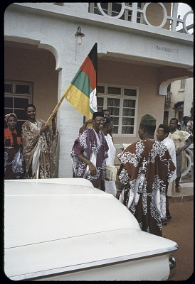 Dr.Nnamdi Azikiwe (in purple robe), Premier of Eastern region, talks to supporters outside his apartment house, Onitsha, Nigeria. [slide]