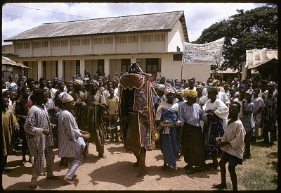 Crowd accompanying Egungun masquerader and his musicians, Ede, Nigeria, [slide]