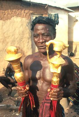 Kouakou Yao, a Baule sculptor, displaying fly-whisks with gold-leafed finials, Yagolikro village, Ivory Coast, [slide]
