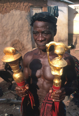Kouakou Yao, a Baule sculptor, displaying fly-whisks with gold-leafed finials, Yagolikro village, Ivory Coast, [slide]