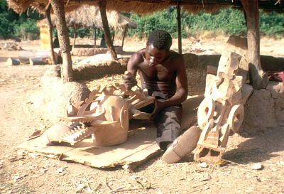 Senufo man carving Wanyugo helmet, near Korhogo, Ivory Coast, [slide]