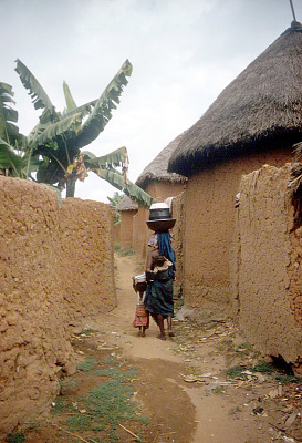 Nupe woman walking in narrow street surrounded by mud wall fences, Bida, Nigeria, [slide]