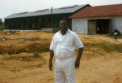 Lumber and rubber businessman Joseph Asaboro, sheds for curing rubber in background, Sapele, Nigeria. [slide]