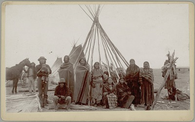 Scalp Cane and his Clan, Most Wearing Blankets, Outside Tipi Framework; Other Tipis, Man with Horse, Wagon, and Children In Travois Basket Behind Them 1889