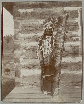 Bullthigh, Keeper (or Pledger?) of Sacred Arrow, in Native Dress with Feather Headdress and Lance Outside Log House 1910