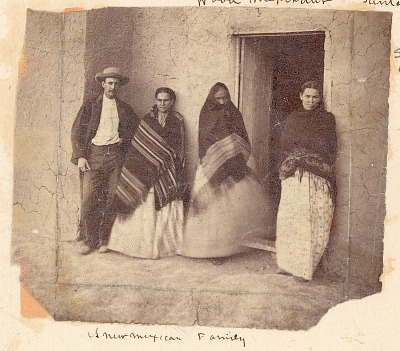 Three Women in Partial Costume and with Man, Outside Doorway of Adobe House n.d