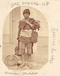 Man, Muleteer, in Costume Carrying Fiber Woven Bag, Outside Stuccoed Building n.d