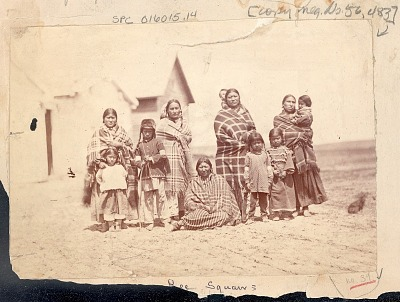 Group of Women and Children in Partial Native Dress, One Girl Wearing Elk Tooth Dress, Outside Row of Wood Frame Structures n.d