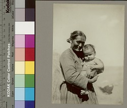 Woman holding infant with clay on cheeks and squash blossom necklace Copyright 15 JAN 1907
