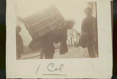 Three Quechua Men in Costume on Cobbled Street; One with Trunk Strapped to Back n.d