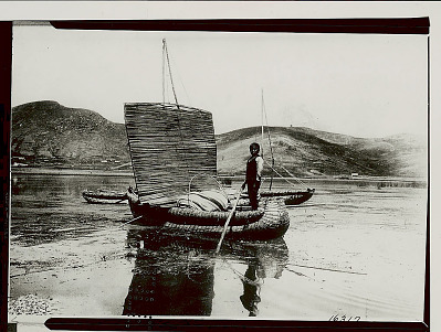 Young Man in Balsa (Reed Boat) with Open Reed Sail; Town And Hills in Distance 1921