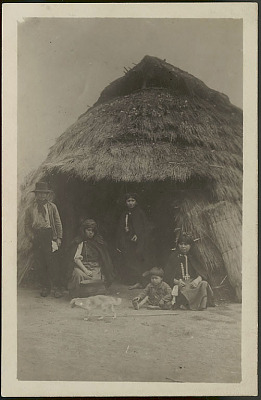 Family Group in Costume Outside Ruka (Pole and Thatch House); Bowl and Dog Nearby n.d