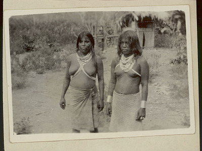 Two Choco Women Wearing Face and Body Paint and in Costume, One With Silver Arm Cuffs, Near Pole Structure with Thatch Roof 1923