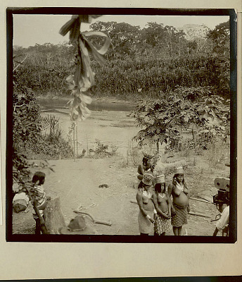 Choco Harvest Festival; Non-Native Man Taking Photo With Camera on Tripod of Three Women in Ceremonial Costume; Two Men in Ceremonial Costume Watching River in Background 1923