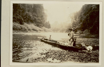 Two Marsh-Darien Expedition Members, R. O. Marsh and Malobury?, and Native Guide with Cargo and Rifle in Dugout Canoe with Motor on River 1923