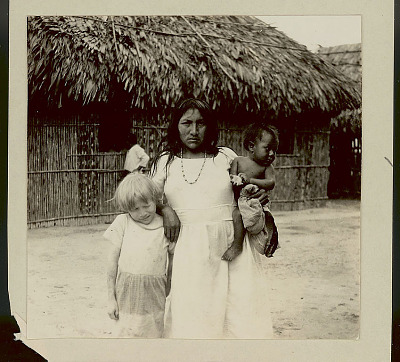 Cuna Woman with Infant and Young Girl, Albino, Outside Pole House with Thatch Roof 1923