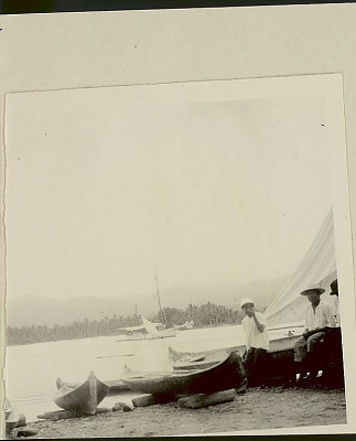 Two Cuna Men in Costume and with Dugout Canoes on Beach; Non-Native ? Boats with Sails in Water 1923